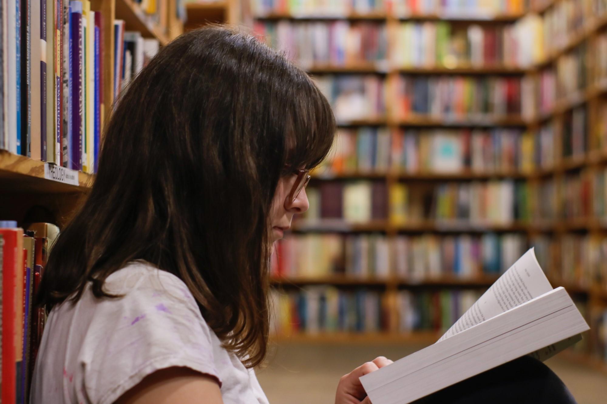 Rapariga a ler no meio de uma biblioteca