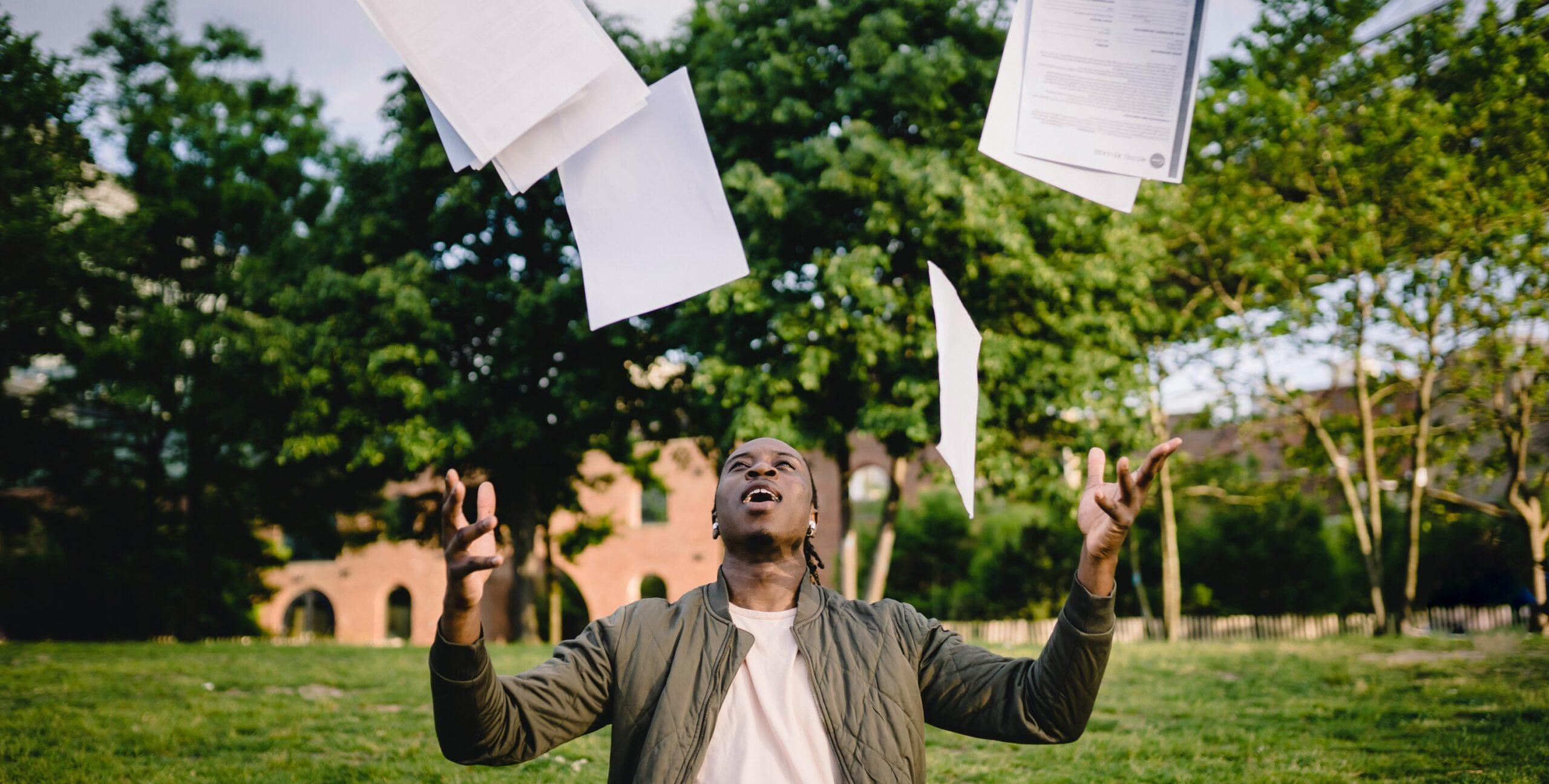 Jovem a lançar papéis ao ar