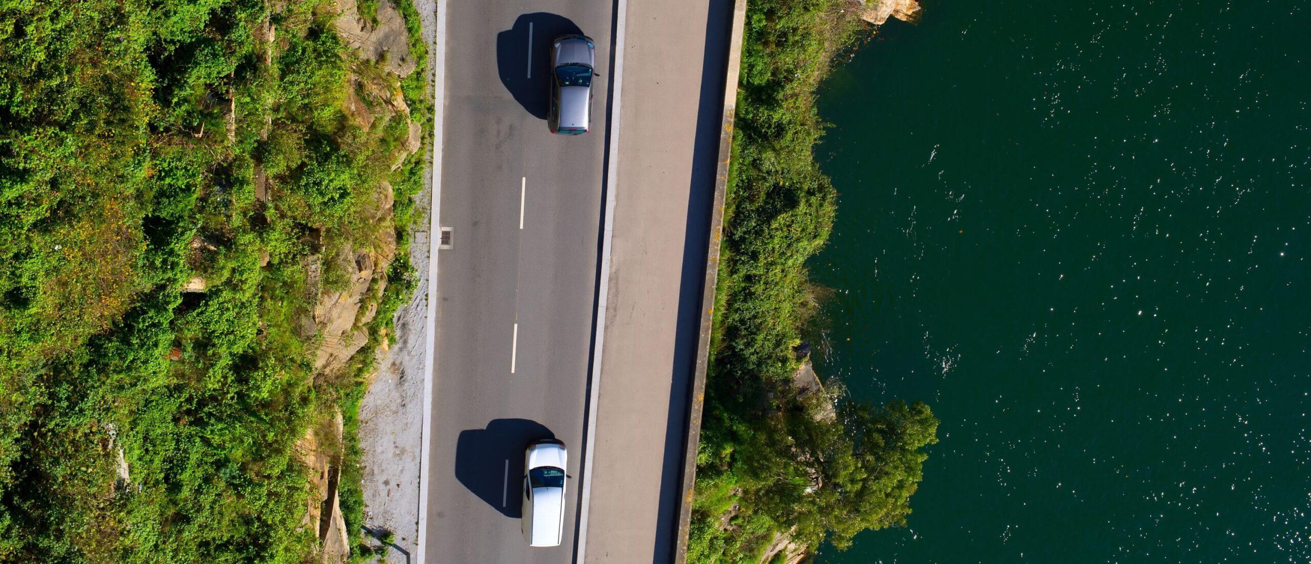 Vista aérea de dois carros numa estrada ao pé do rio