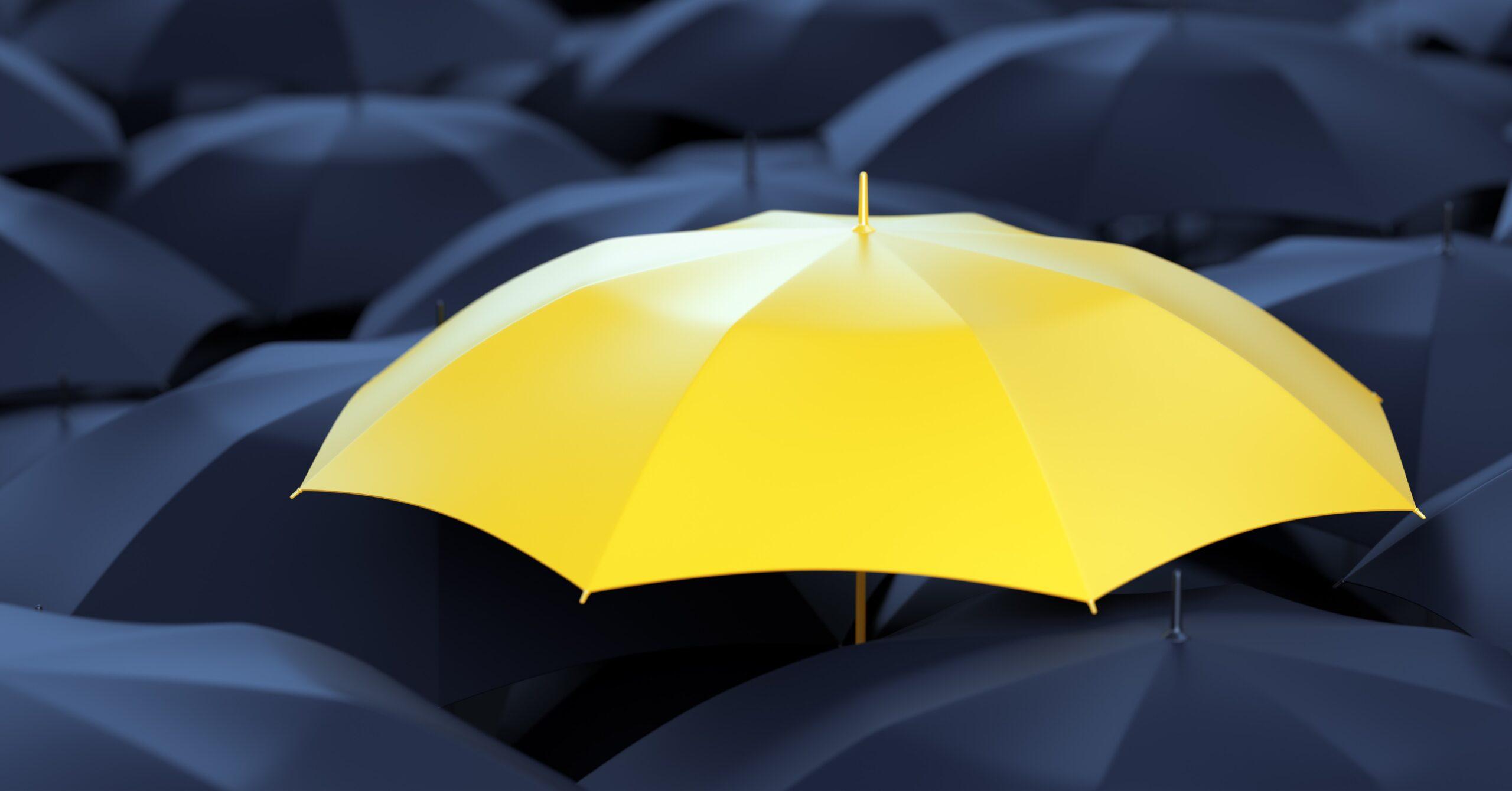 Chapéu de chuva amarelo no meio de chapéus pretos