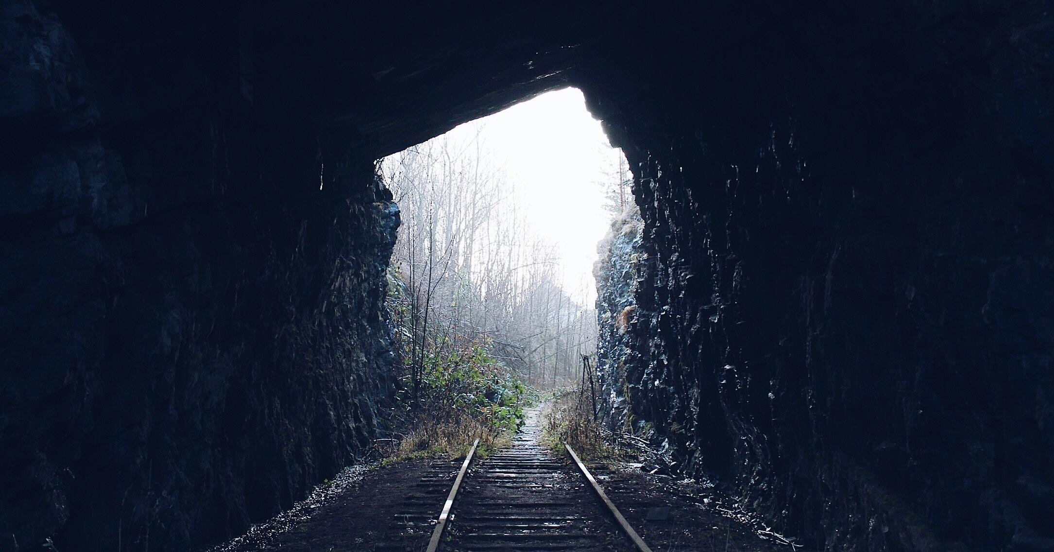 Luz ao fundo do túnel com linha de comboio
