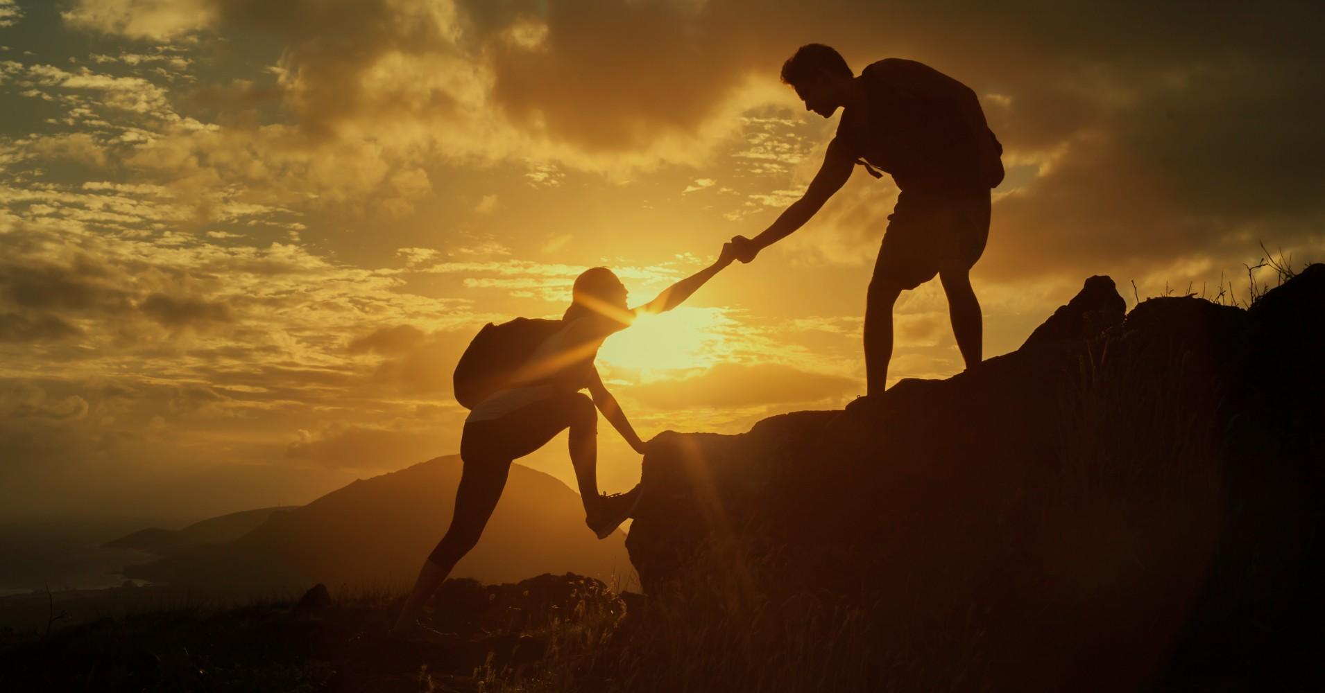 Um montanhista a ajudar outro a subir a uma rocha ao pôr-do-sol