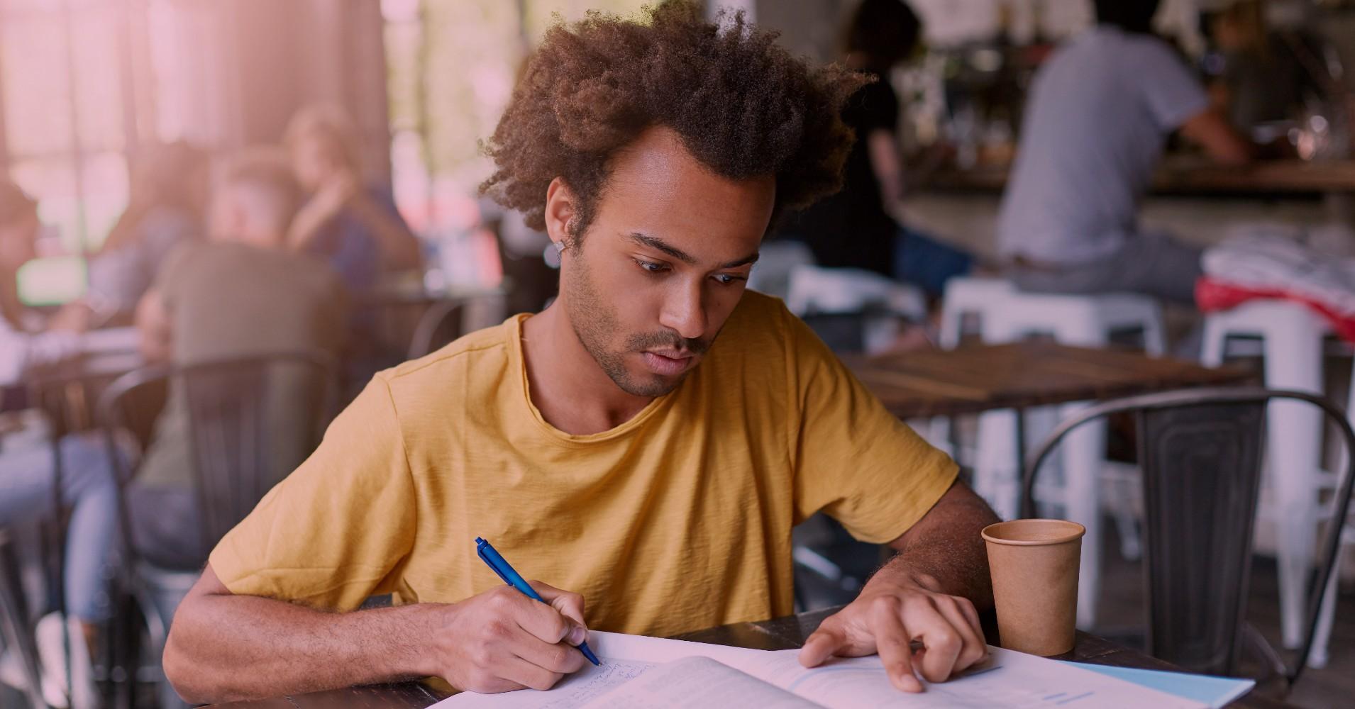 Rapaz a estudar num café