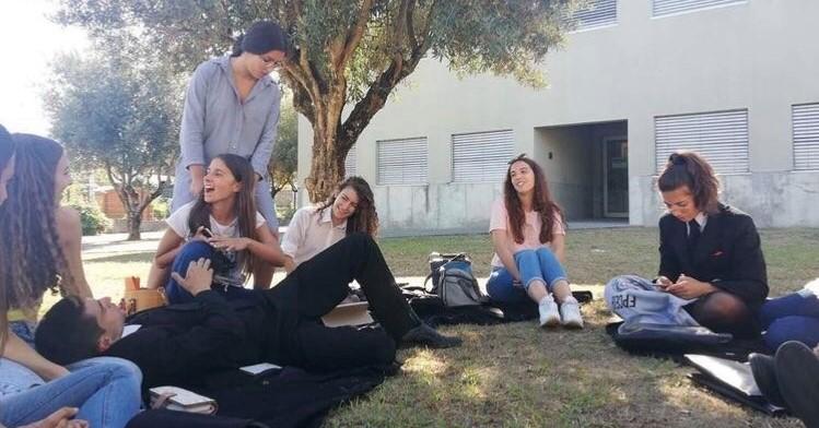 Grupo de jovens sentados e deitados a conversar na relva, num dia solarengo