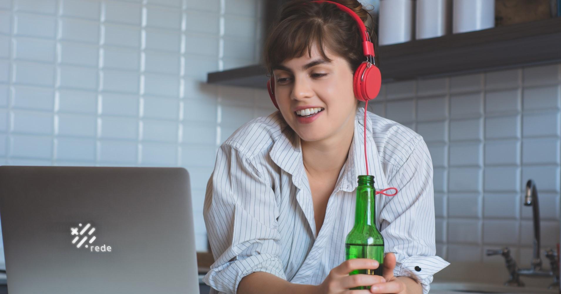Rapariga a beber cerveja enquanto participa em reunião no computador