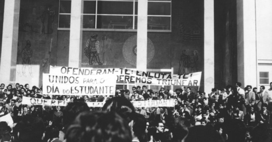 """Manifestação estudantil de 24 de março de 1962, em frente à reitoria da Universidade De Lisboa, onde se vê uma multidão de jovens empunhando 3 tarjas: """"Unidos para o dia do Estudante"""", """"ofenderam-te?: Enluta-te (...)"""" e outro não percetível"""