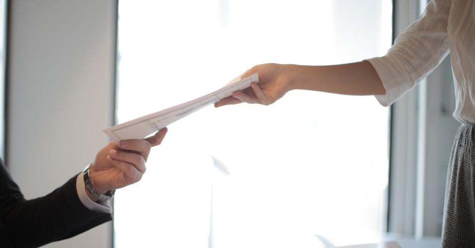 Pessoa em entrevista de emprego a entregar CV depois de acabar o curso