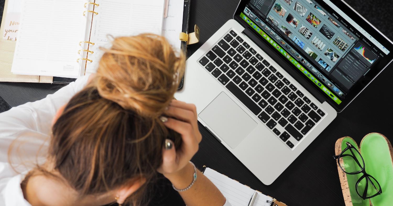 Rapariga com computador à frente e mão na cabeça, mostrando ansiedade durante o confinamento