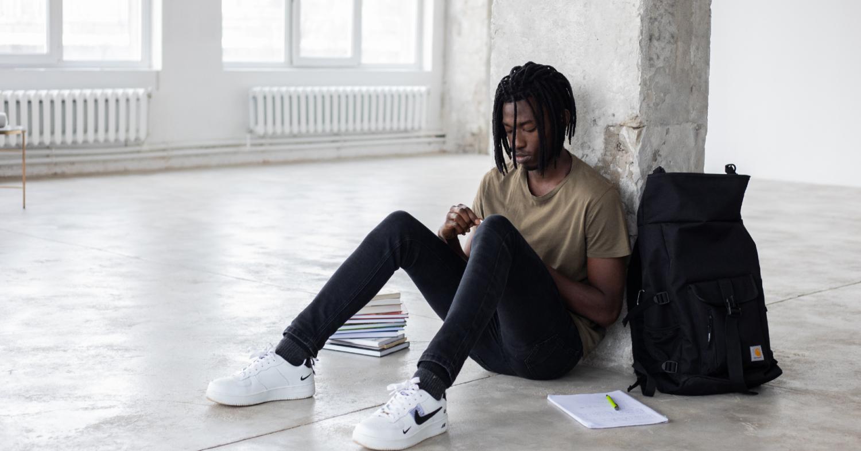 Rapaz sentado no chão com livros à volta