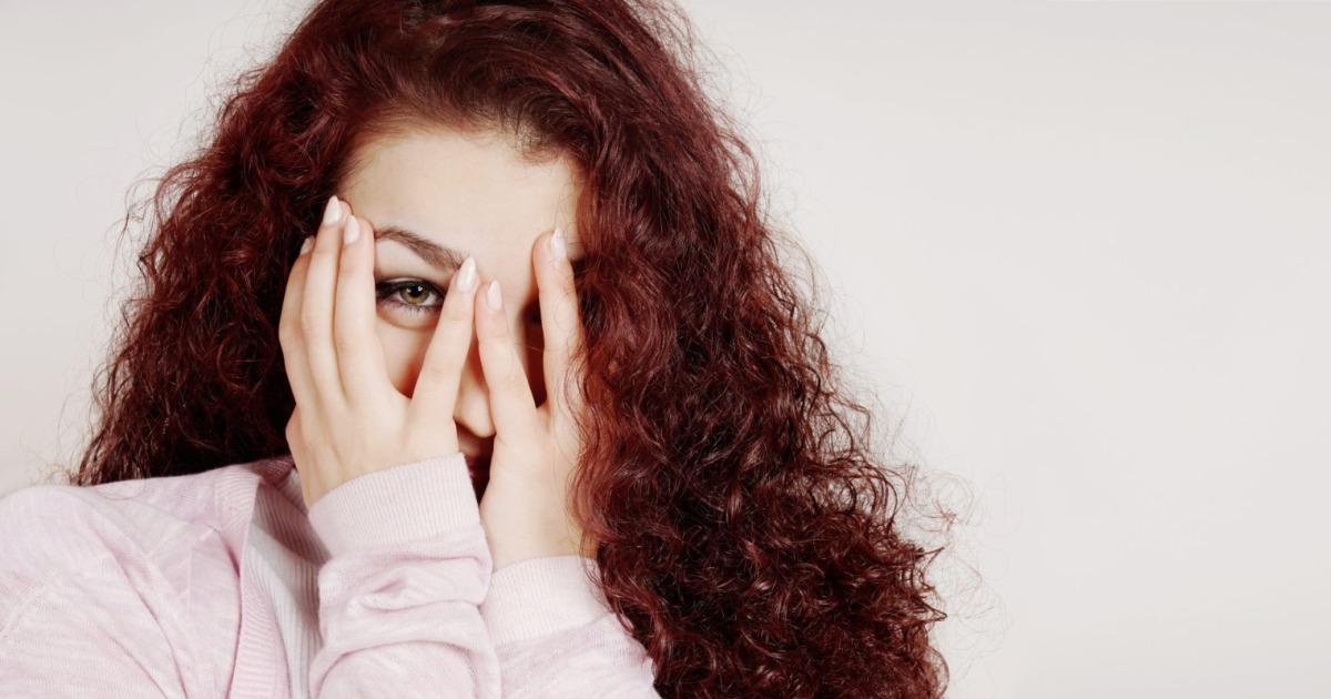 Rapariga a esconder a cara com as mãos