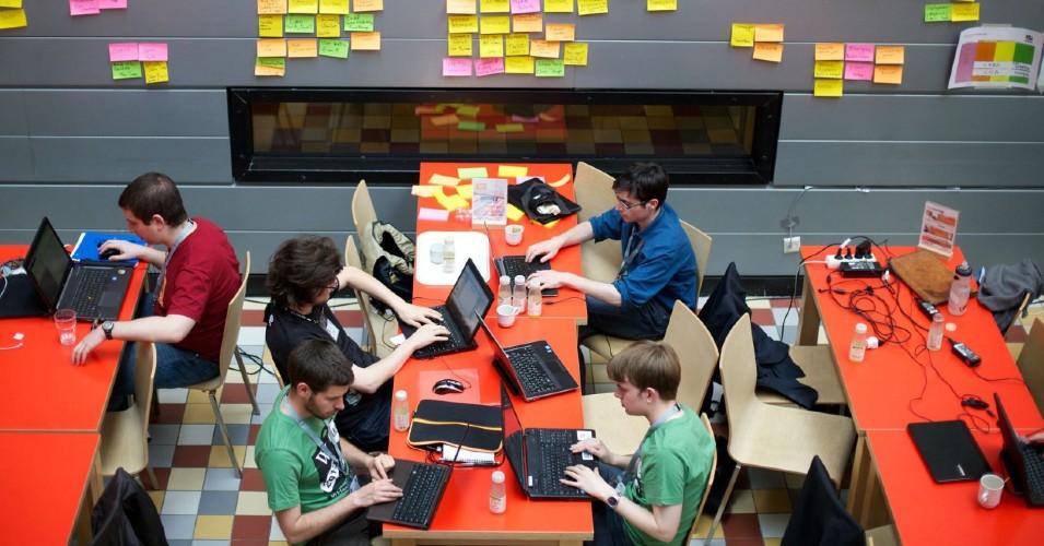 Jovens rapazes sentados, a trabalhar em frente a computadores, visto de cima