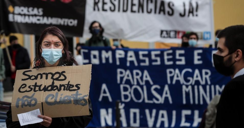 """Manifestação de estudantes com destaque para uma rapariga que segura um cartaz a dizer """"Somos estudantes, não clientes"""""""
