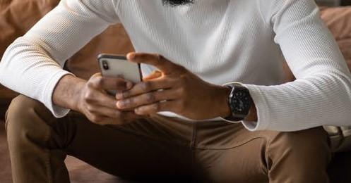 Mãos de homem a segurar em telemóvel