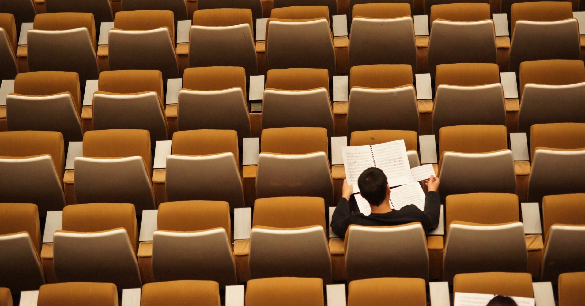 Estudante sentado em anfiteatro vazio visto de cima