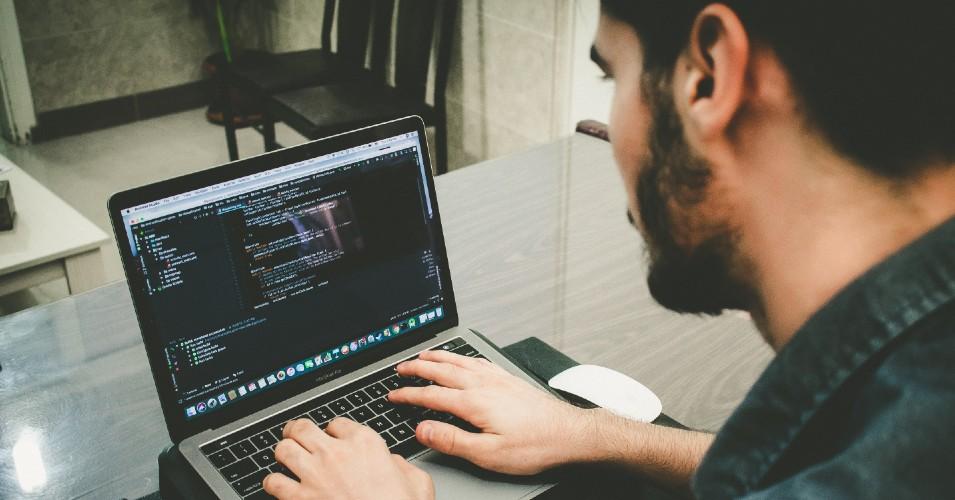 Rapaz sentado com computador portátil no colo a programar