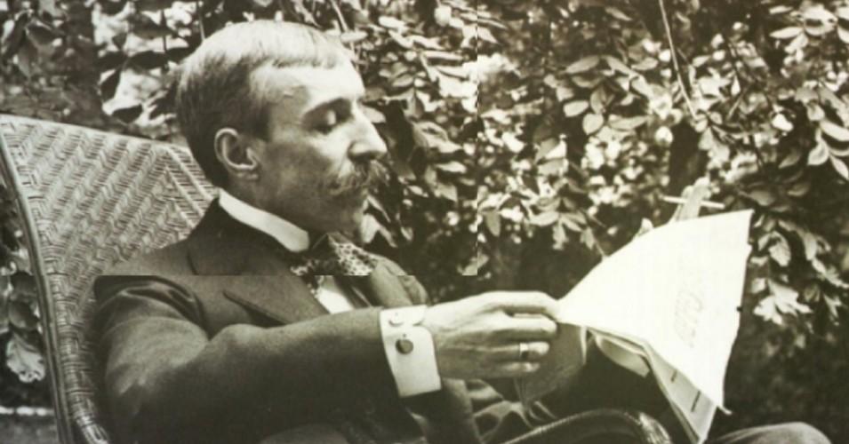 Fotografia de Eça de Queirós, sentado, a ler o jornal