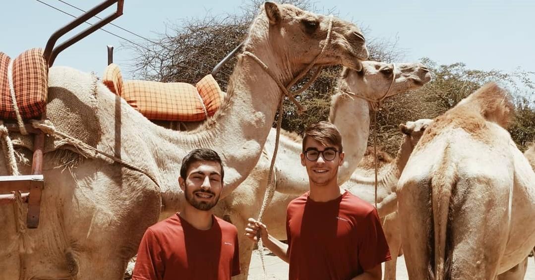 Dois jovens posam para a foto em frente a dois camelos, durante a realização do seu Gap Year