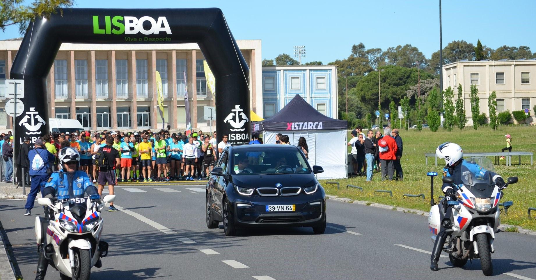 Dezenas de pessoas na linha de partida de uma corrida, na cidade universitária em Lisboa. à frente vemos duas motas da PSP e um carro de suporte
