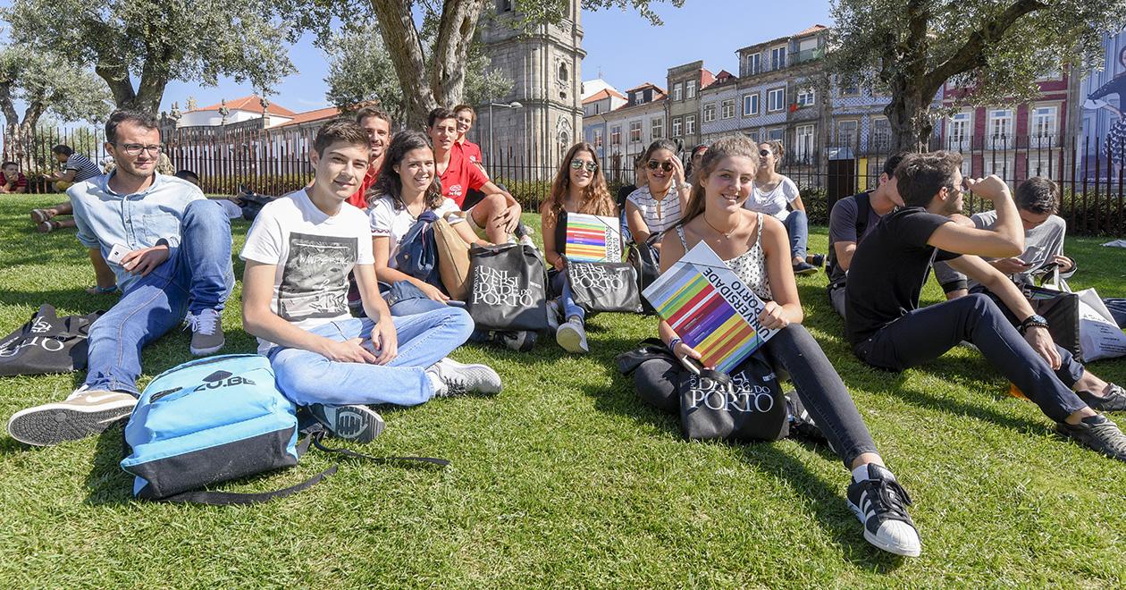 Grupo de estudantes de primeiro ano de faculdade sentados na relva, junto à torre dos clérigos no porto, ostentanto capas arquivadoras e sacos da universidade do Porto