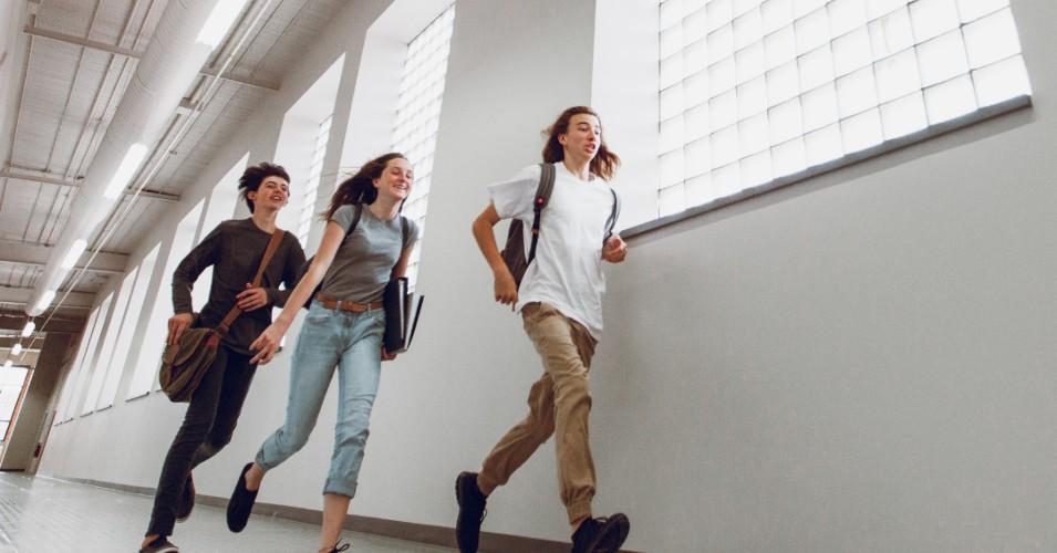 3 alunos a correr, atrasdados para a aula