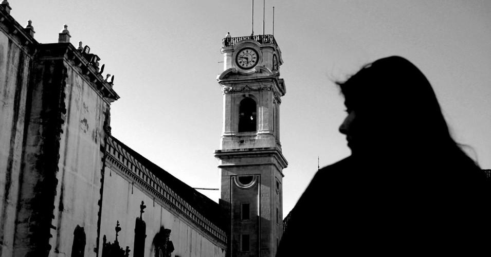 Estudante trajada em contraste com a torre da Cabra, na Unviersidade de Coimbra