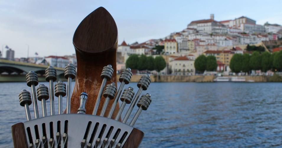 afinadores de uma guitarra portuguesa com Coimbra e o rio Mondego como pano de fundo
