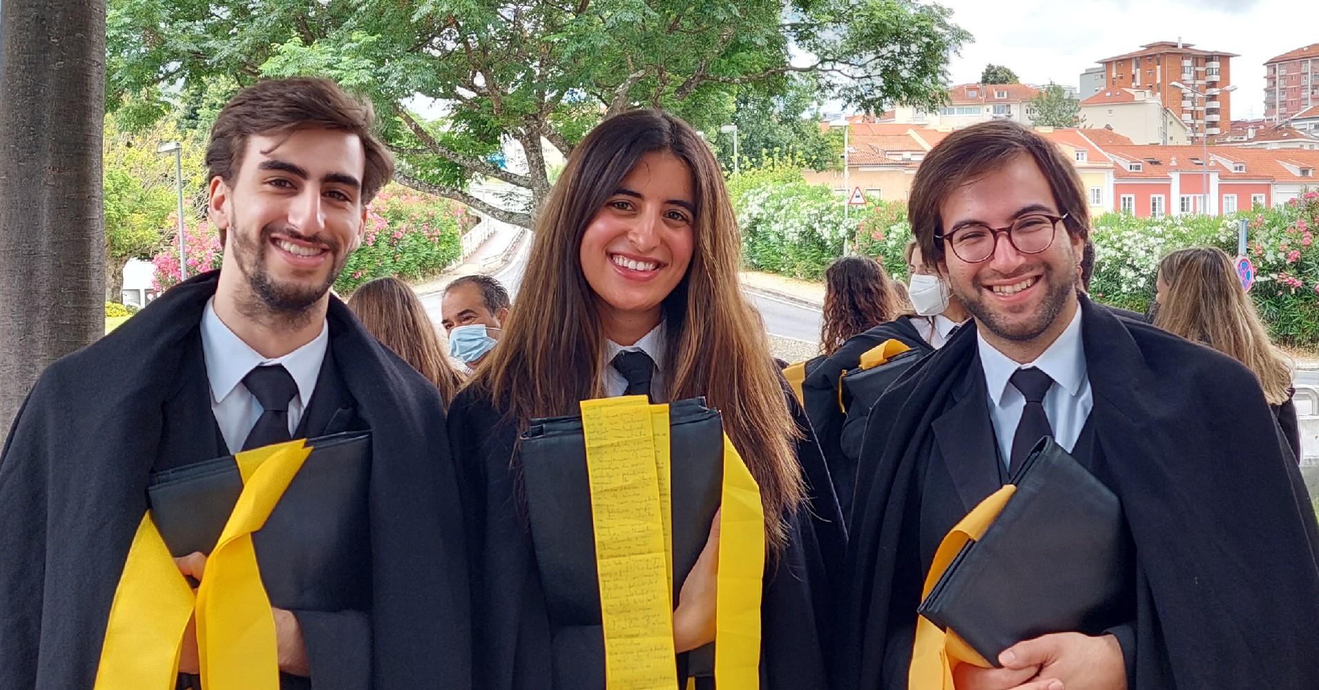 3 Estudantes finalistas a sorrir para a foto com fitas amarelas na pasta