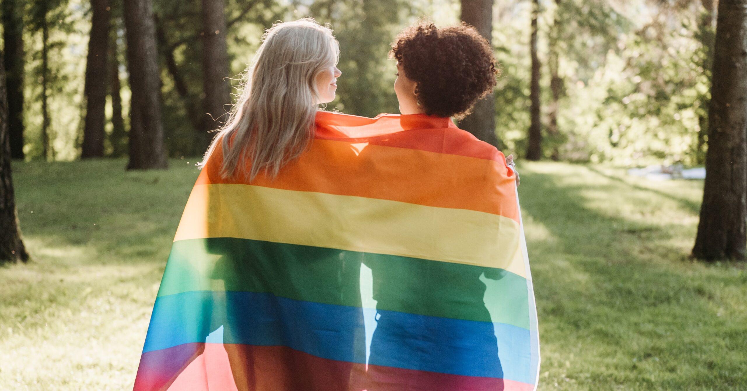 Duas raparigas que caminham na direção contrária, enverganho uma bandeira do orgulho LGBT pelas costas