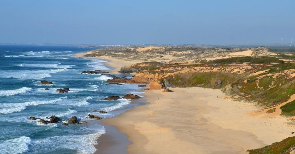 vista panorâmica da praia com mar a esquerda e areia e relva a direita